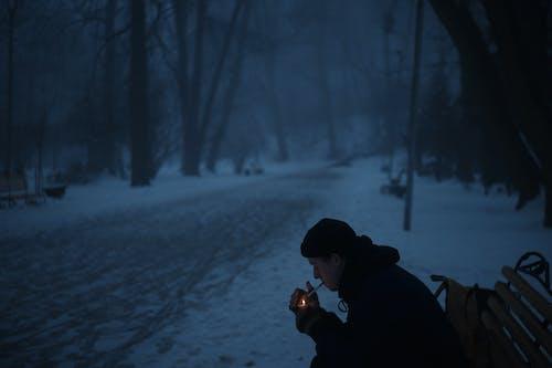 Man in Black Hoodie Holding Brown String Lights