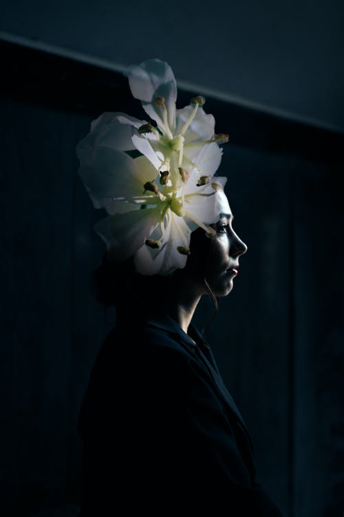 Woman covering head with delicate flowers