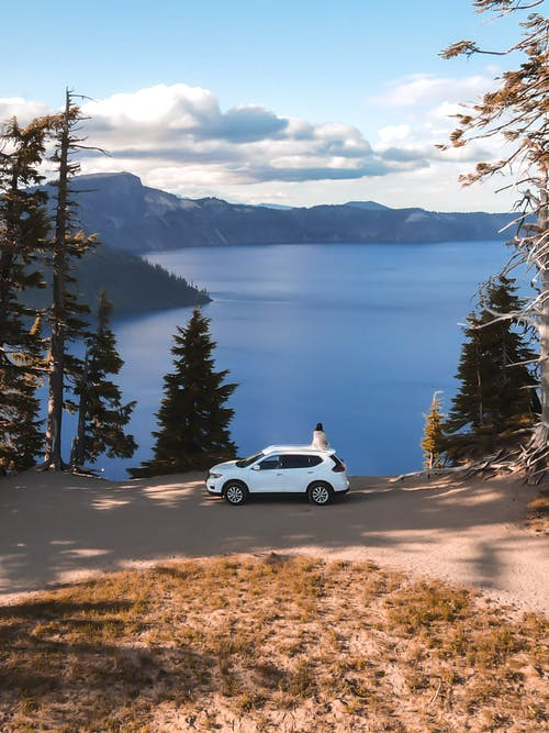 Unrecognizable tourist standing near car parked above picturesque lake in highland