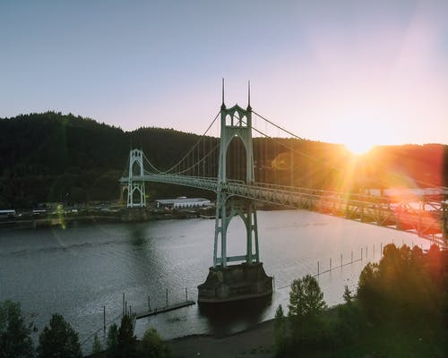 Magnificent scenery of aged St Johns Bridge crossing rippling river surrounded by hills with lush green woods against cloudless sunset sky in Portland