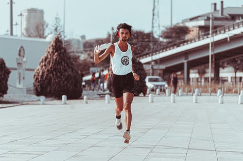 Active sportsman running along paved street