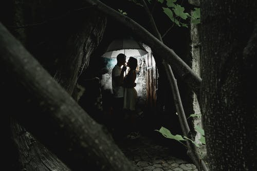 Side view of full length man and woman wearing casual outfit cuddling in smoke in dark room in back lit
