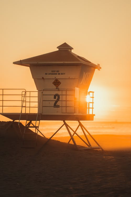 White Lifeguard Station on Beach during Sunset