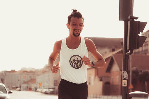 Positive muscular sportsman in activewear jogging along street in sunny day in city