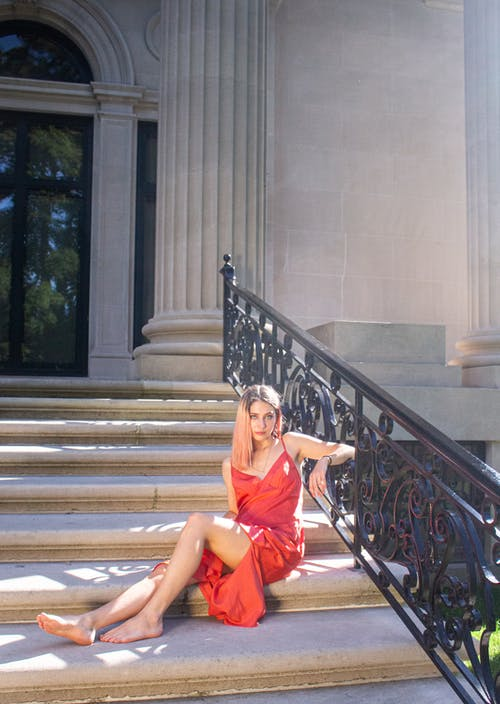Woman in Orange Dress Sitting on Staircase