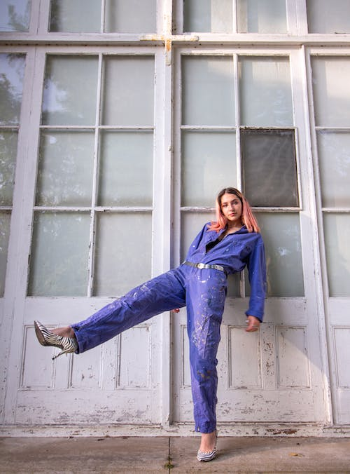 Woman in Blue Denim Jacket and Blue Denim Jeans Standing Beside White Wooden Window