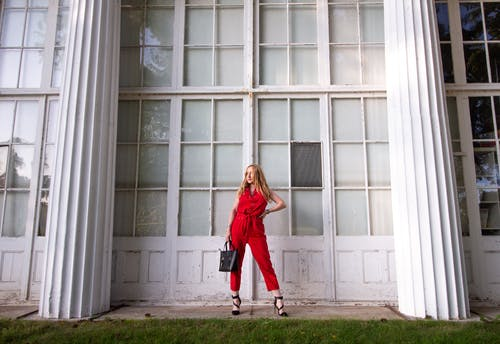 Woman in Red Coat Standing in Front of White Wooden Window