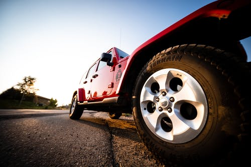 Ground level of red all terrain vehicle standing on road in countryside at sunny day