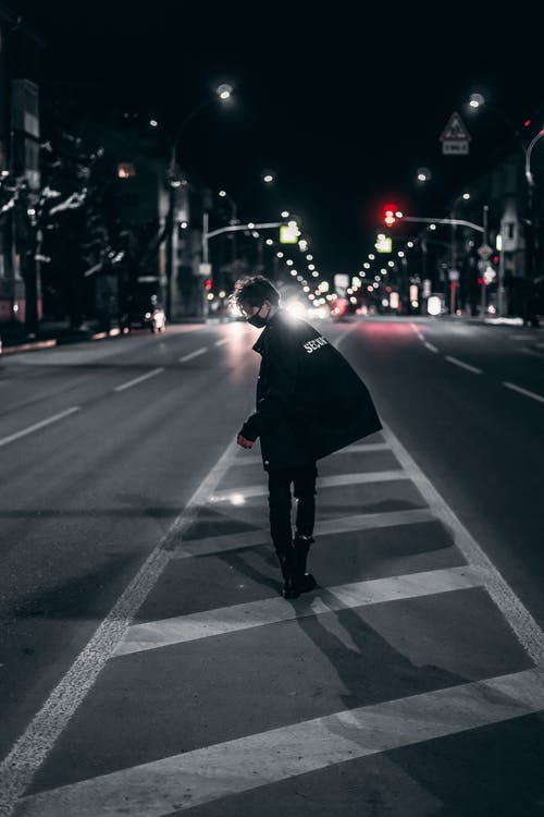 Man in Black Jacket and Black Pants Standing on Pedestrian Lane during Night Time