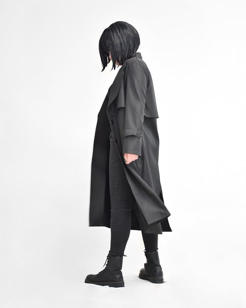 Anonymous model in stylish black apparel on white background
