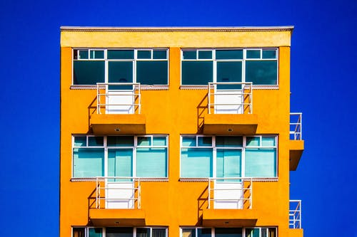 Facade of contemporary yellow residential building on sunny day