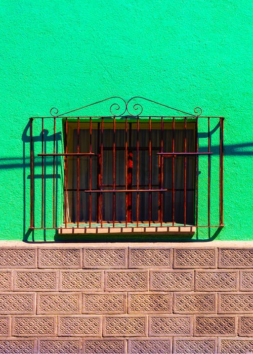 Small window of traditional residential house with metal grid
