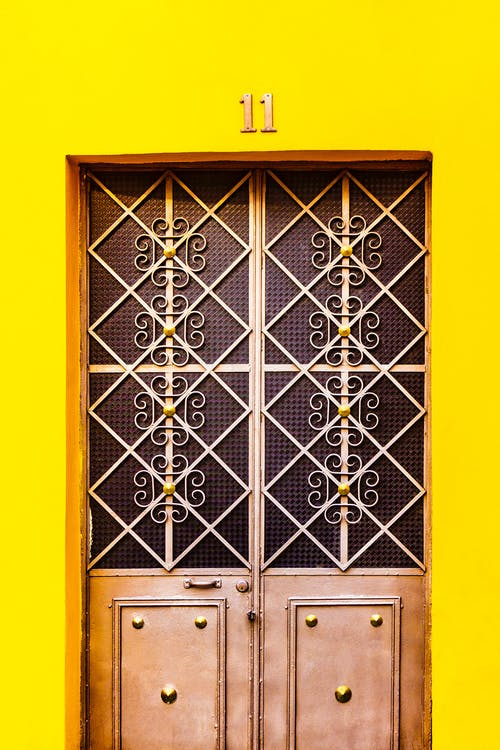 Aged yellow building with wooden door decorated with ornamental shutters