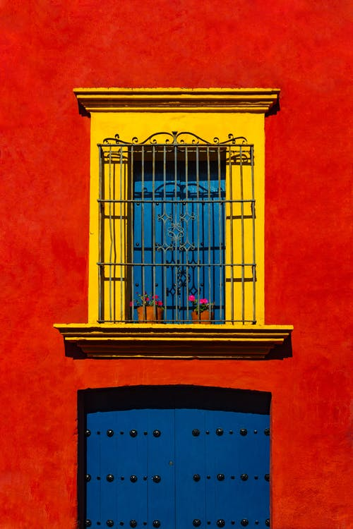 Exterior of bright red colored wall of house with window with yellow shutters and metal bar above door in street in daylight