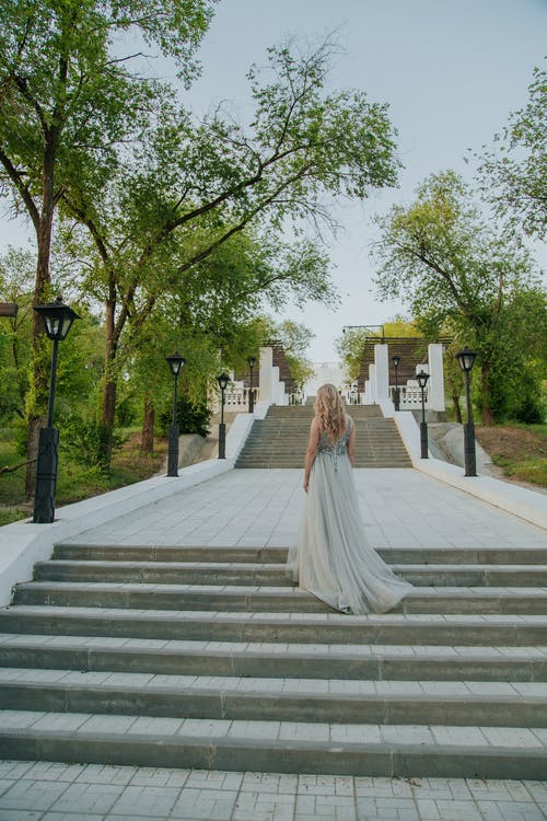 Woman wearing long bridal dress standing on stairs
