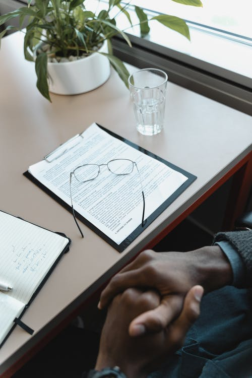 Person Holding White Paper on Table