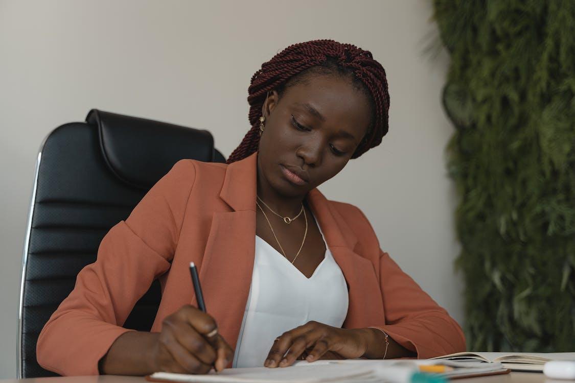 Woman in Orange Blazer Holding Pen