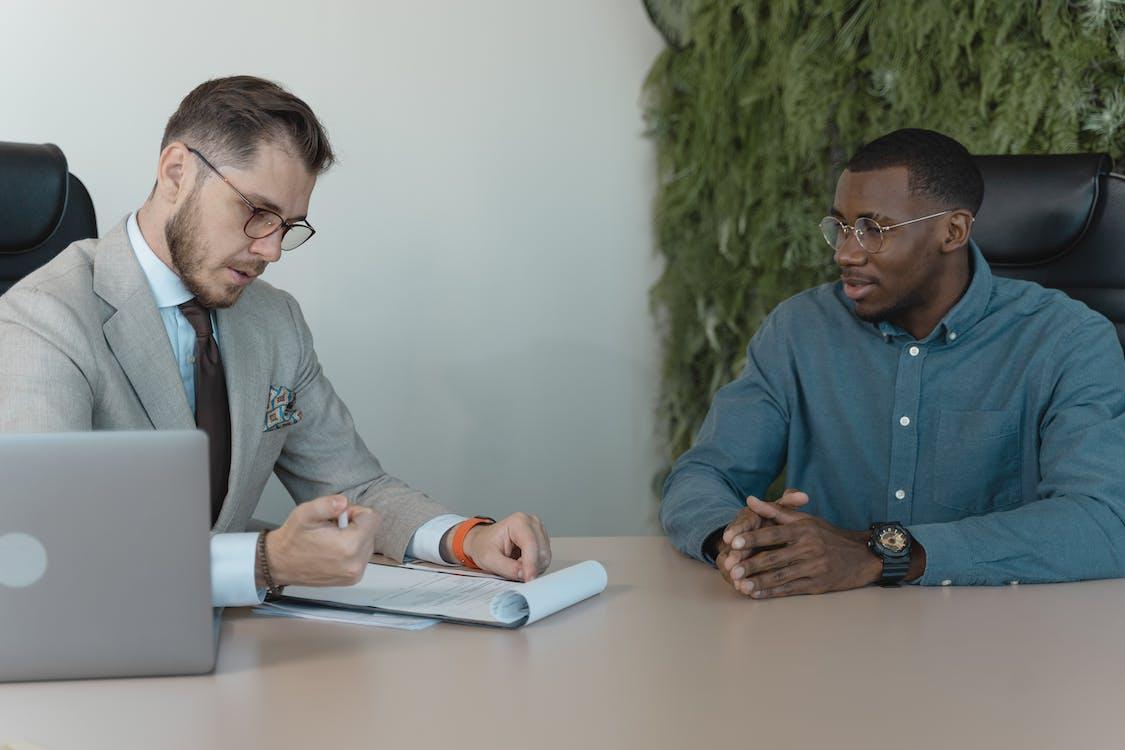 Man in Blue Dress Shirt Reading the Resume