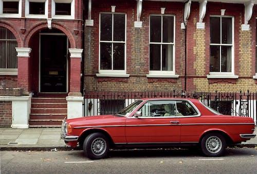 Red Sedan Parked Beside Brown Brick Building