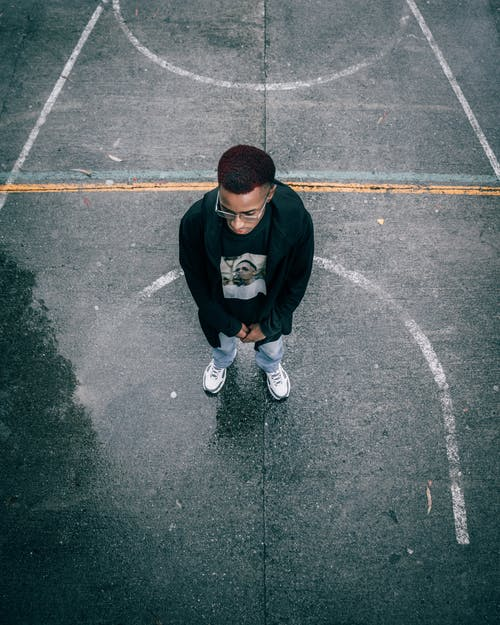 Contemplative black man standing on wet asphalt sports ground