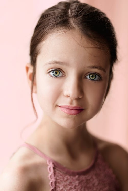 Charming positive little girl in pink lace clothes looking at camera against blurred light background in studio