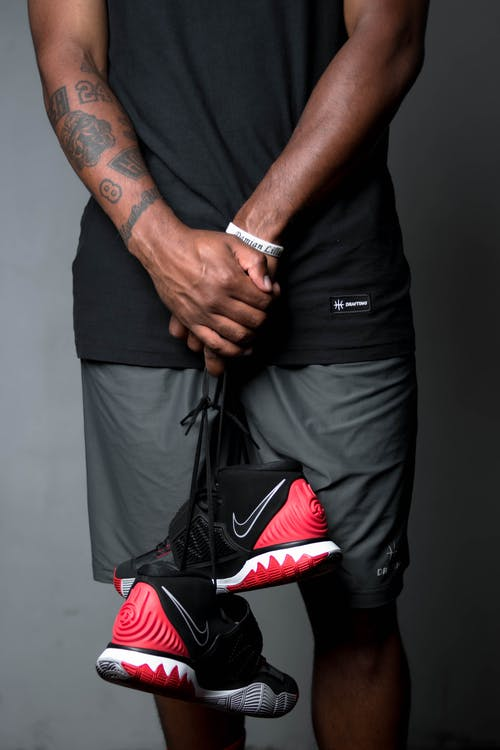 Man in Black Nike Shirt and Black Pants With Black Red Nike Basketball Shoes