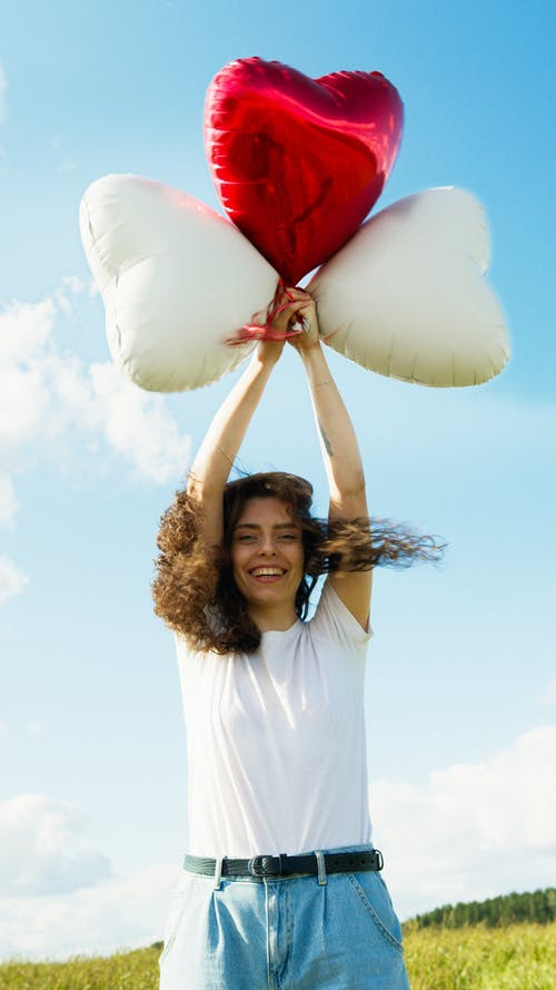 Woman in White Long Sleeve Shirt Holding White and Red Balloons