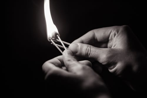 Person Holding Lighted Match Stick