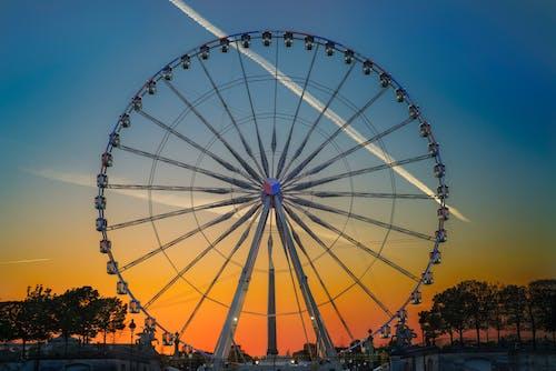 Huge Ferris wheel in modern amusement park against bright colorful sky at sundown