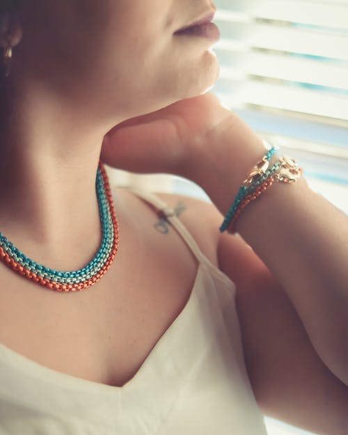 Woman in White Tank Top Wearing Blue Beaded Necklace