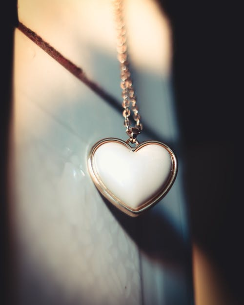 Silver Heart Pendant Necklace on Black Surface