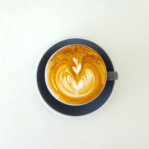 Coffee cup with latte art froth on white surface