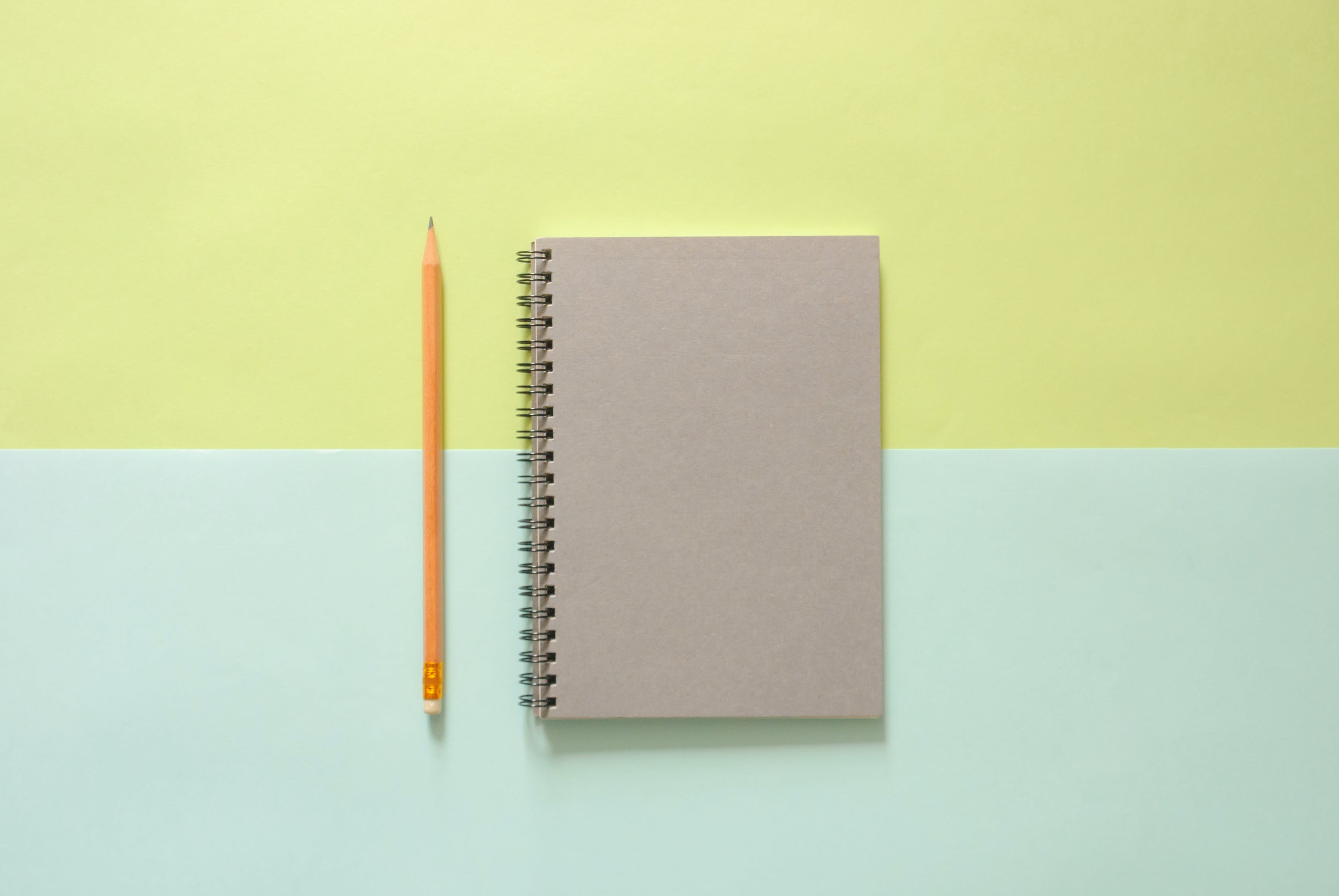 White Spiral Notebook Beside Orange Pencil