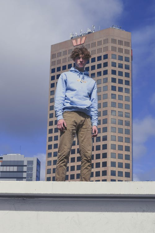 Man in Blue Dress Shirt and Brown Pants Sitting on White Concrete Wall