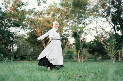 Woman in White Robe Holding White Textile Standing on Green Grass Field