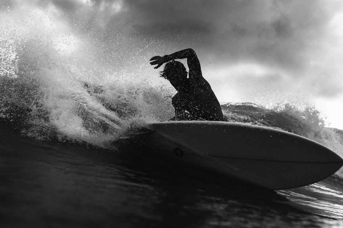 Black and white of anonymous male surfer riding on wave with raised arm against cloudy sky in stormy weather outside
