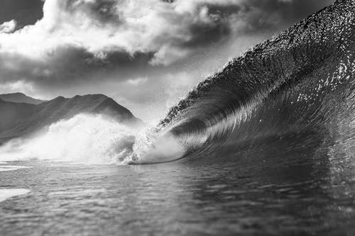 Black and white of foamy wave falling into ocean with splashes against cloudy sky in summer day in nature outside