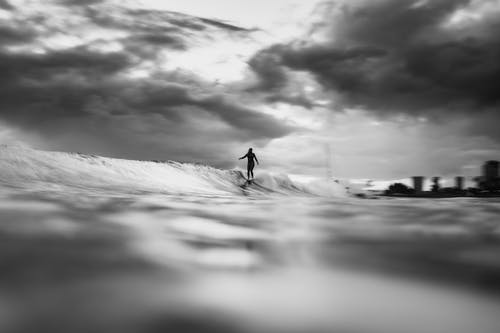 Black and white of anonymous distant surfer surfer riding on wave on surfboard in sea against cloudy sky in tropical country