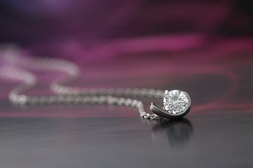 Silver Round Pendant Necklace on Gray Surface