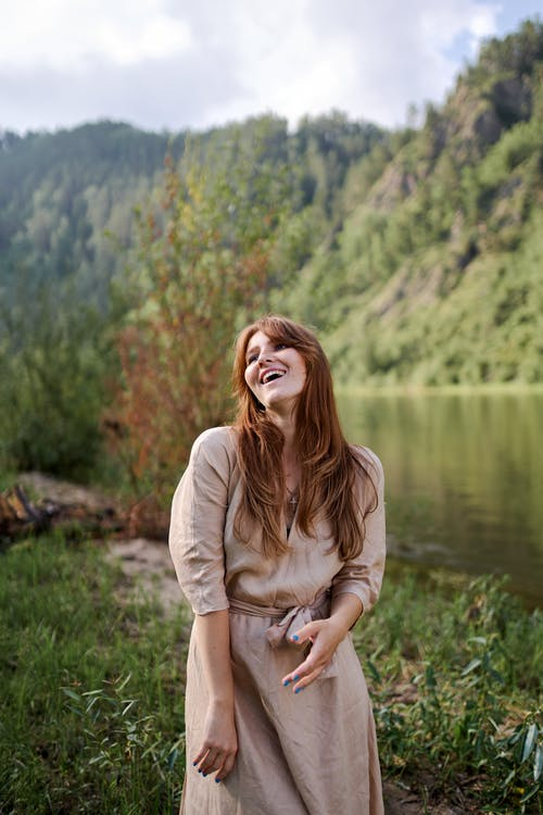 Happy woman against greenery mountain and pond