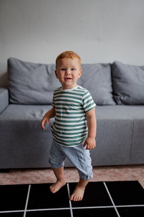 Cute little boy near sofa in living room