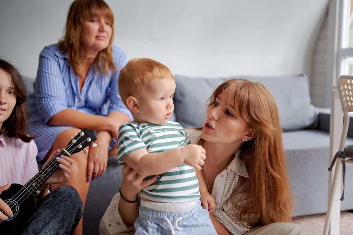 Moeder Met Zoontje In De Buurt Van Vrouwelijke Familieleden In De Woonkamer