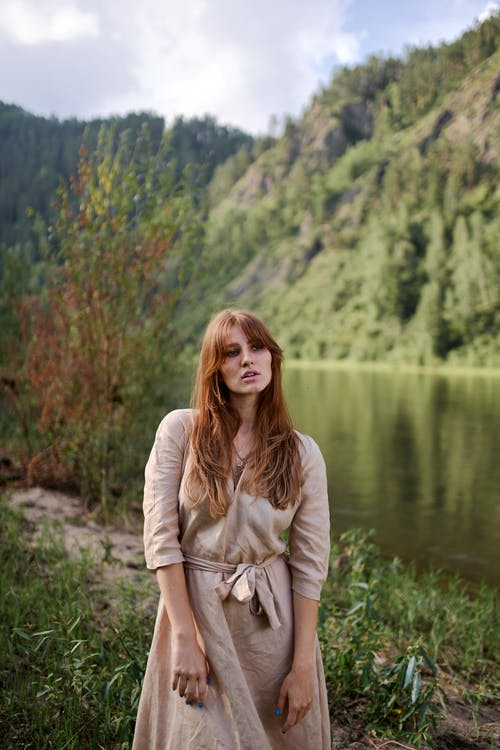 Dreamy woman on river coast against mount in summer