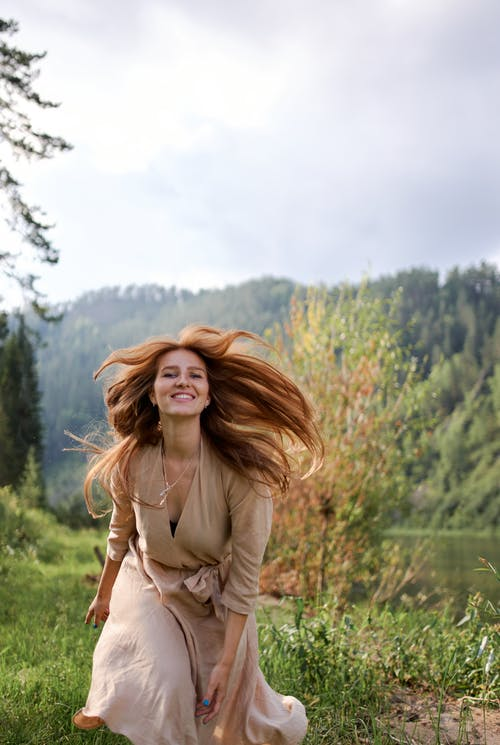 Young cheerful female in dress looking at camera with toothy smile near pond and mount under cloudy sky