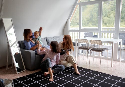 Grandmother playing with grandson near daughters on carpet