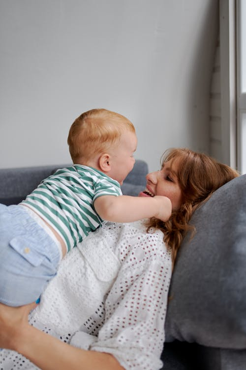 Smiling woman with little boy on couch