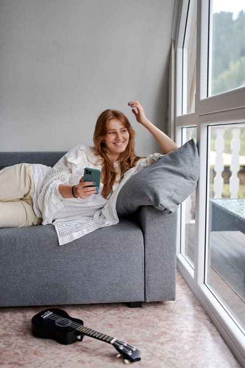 Young content female with cellphone resting on comfortable couch near ukulele on floor and glass wall while looking away