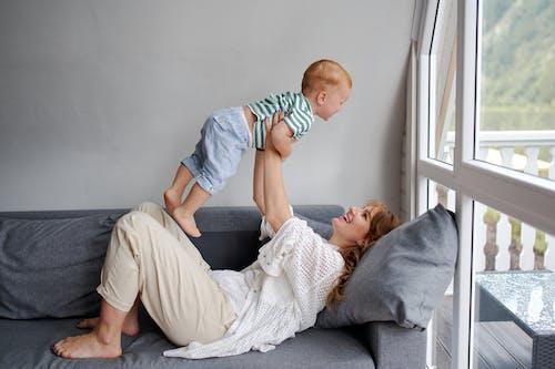 Mujer Alegre Criar A Un Bebé Irreconocible En El Sofá En Casa