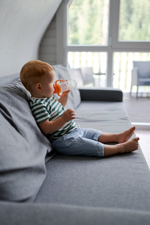 Cute toddler child drinking water on sofa in house