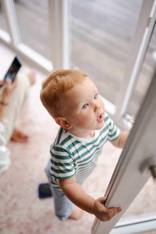 From above of little boy in striped t shirt and jeans opening door in surprise